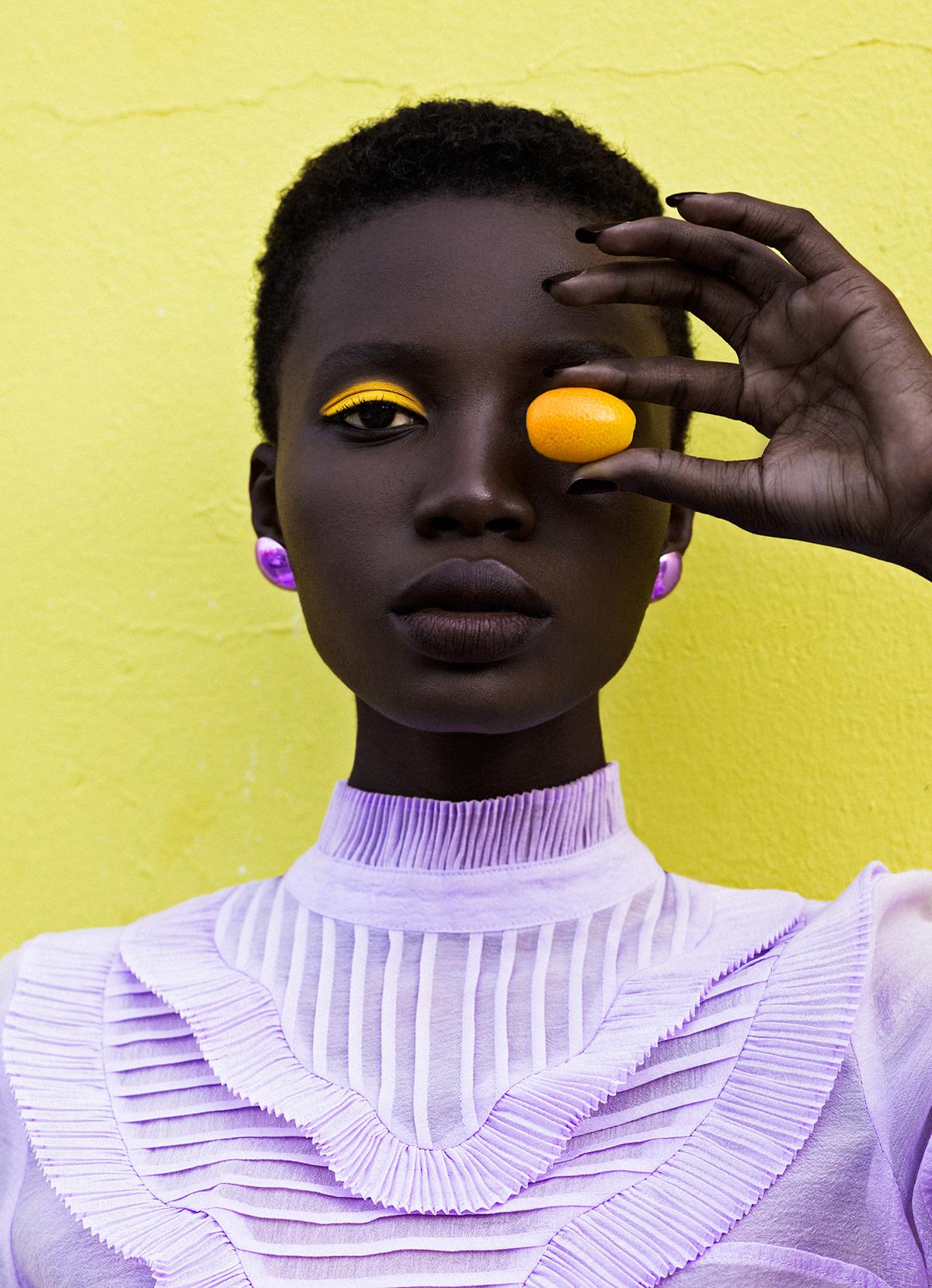 Donna con camicetta e orecchini viola con figura gialla in mano.