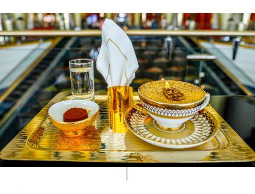 Taszas de café sobre charola dorada y vaso con agua.