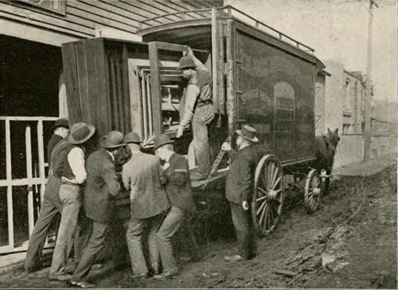 Groep mannen die materiaal in de rug van een vrachtwagen vervoeren.