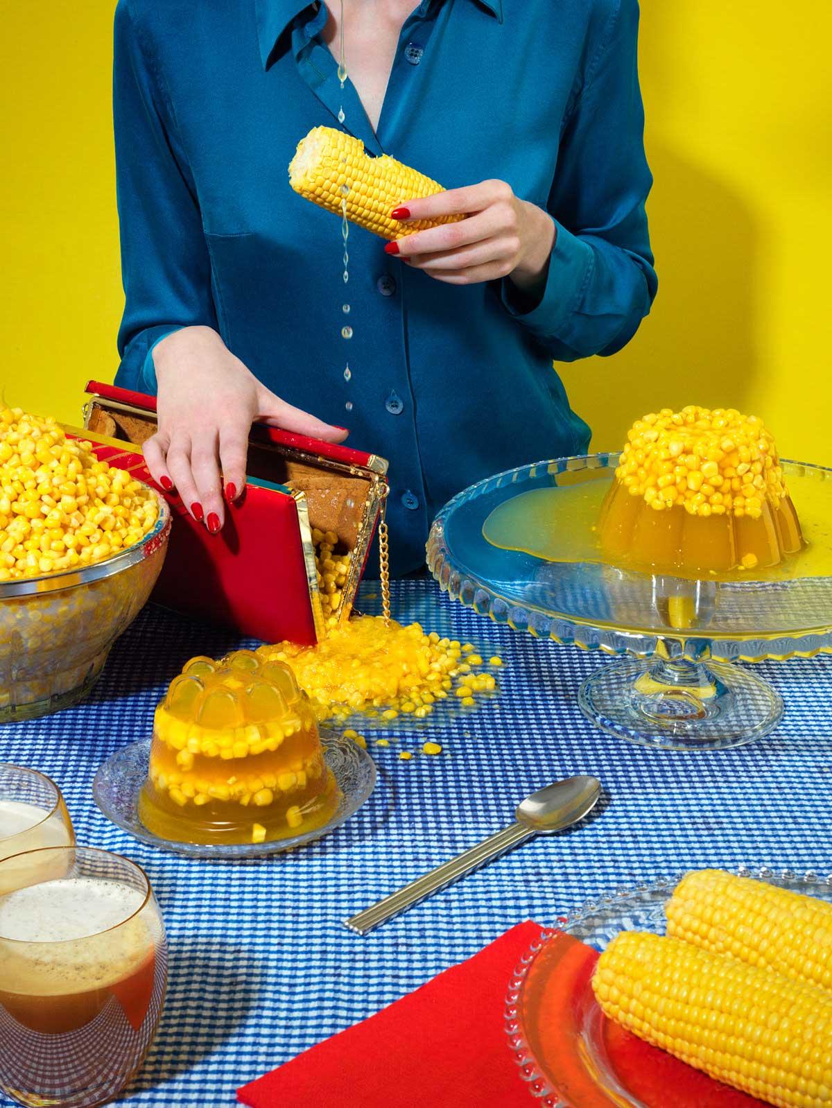 Mujer con blusa azul, bolso rojo, mazorcas y granos de maíz.