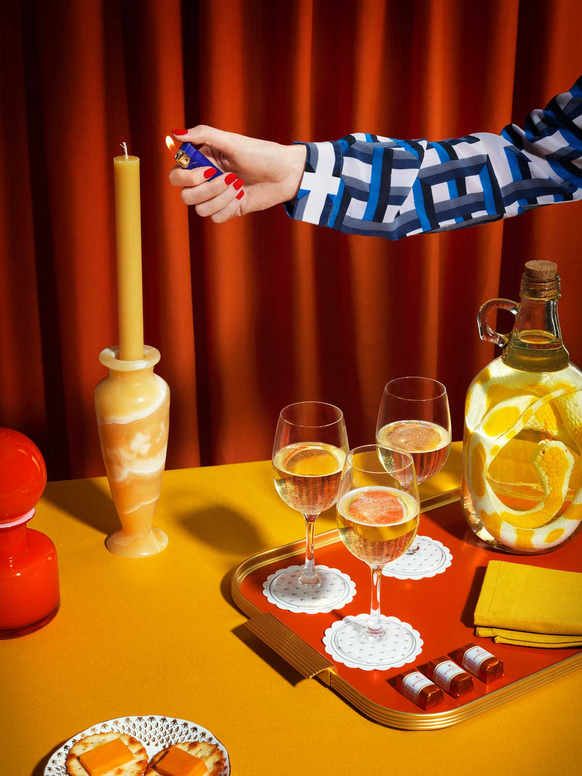 Cortina roja, mesa amarilla, vela, copas, charola y brazo sosteniendo un encendedor.