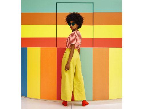 लाल जूते, पीले पैंट और लाल और सफेद धारीदार ब्लाउज वाली महिला।
