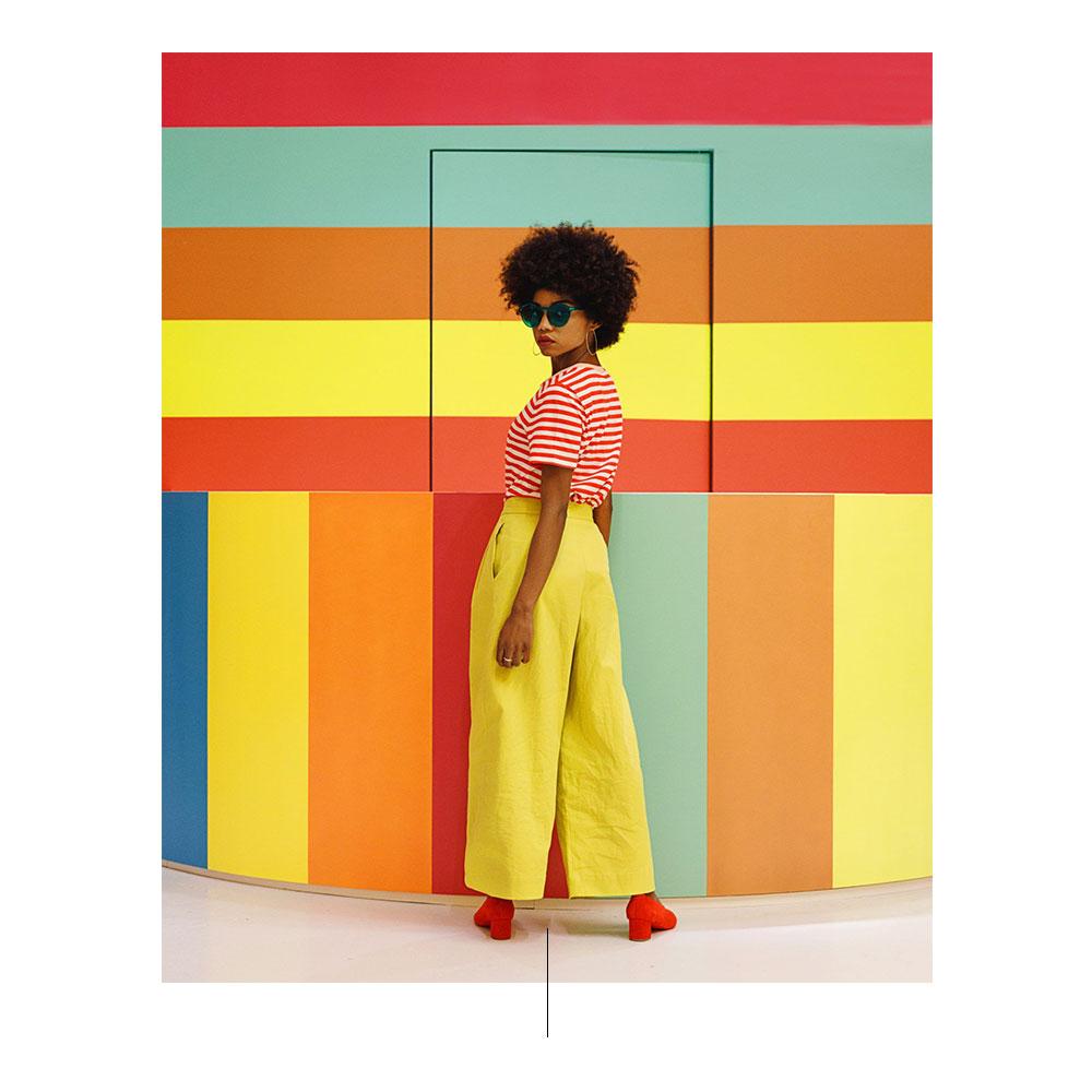 امرأة مع أحذية حمراء وسروالا صفراء وبلوزة مخططة حمراء وبيضاء.