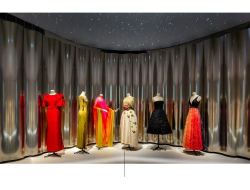 Seks mannequins med flerfargete kjoler.