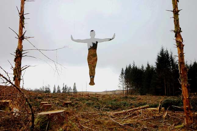 Refleksjon av person i midten av et felt med grener av trær.