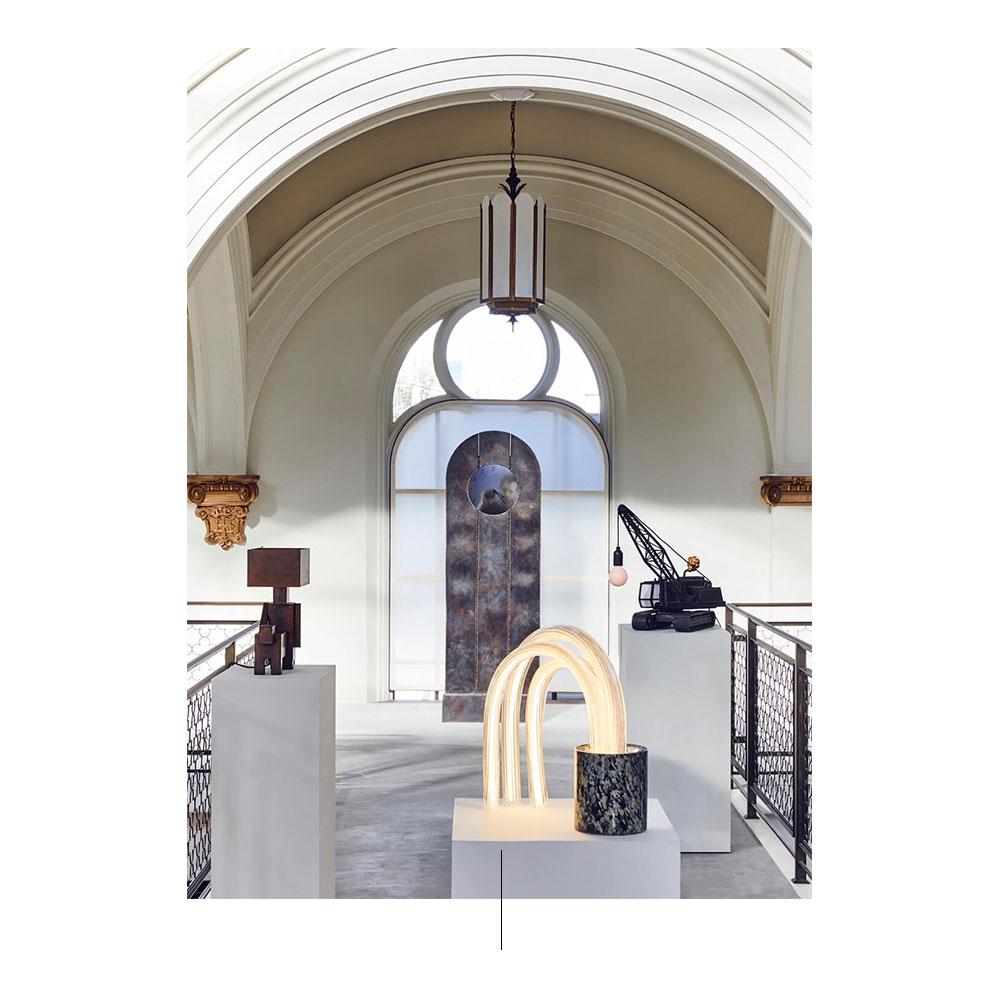 Tres esculturas sobre estantes blancos, lámpara y barandales.