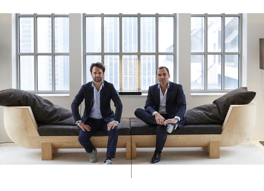 Dos hombres sentados en un sillón, ventanas y pared blanca.