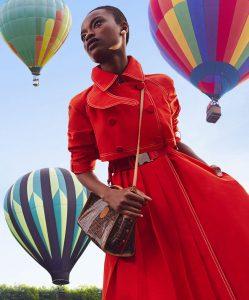 Mujer con vestido rojo y tres globos aerostáticos.