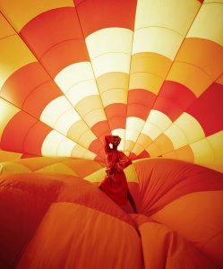 Interior de globo aerostático de tonalidades narajas y mujer con vestido rojo.