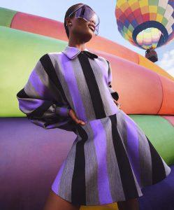 Mujer con vestido a rayas gris, morado y negro, globo aerostático.