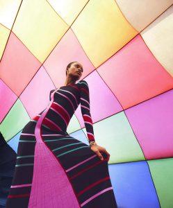 Mujer con vestido negro y rosa con fondo de globo aerostático.