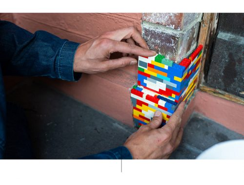 Handen met een stapel Lego-stukken.