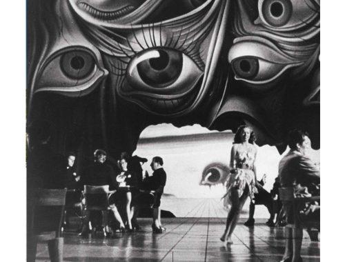 Fotografía en blanco y negro de personas en un salón con fondo de pintura de ojos.