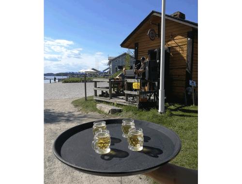 Mesa con tarros de cerveza y cabaña al fondo.