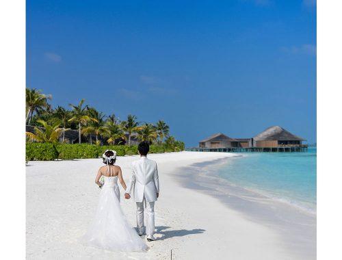 Hombre y mujer caminando sobre la arena a la orilla del mar.