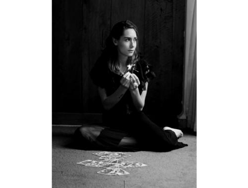 Mujer vestida de negro sentada en el suelo.