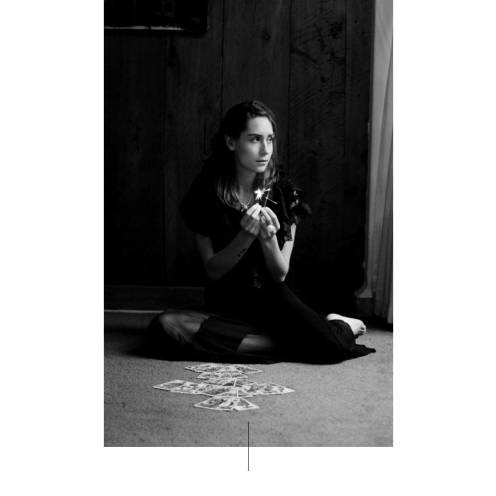 Vrouw, gekleed in zwarte zittend op de vloer.