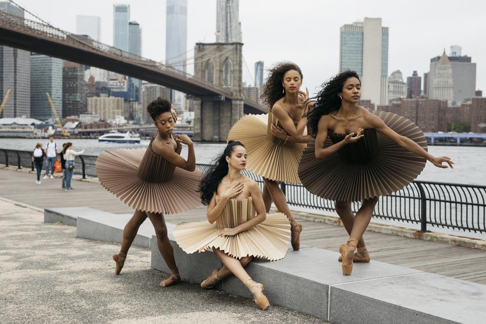 Vier ballerina's op de stoep voor brug en gebouwen.
