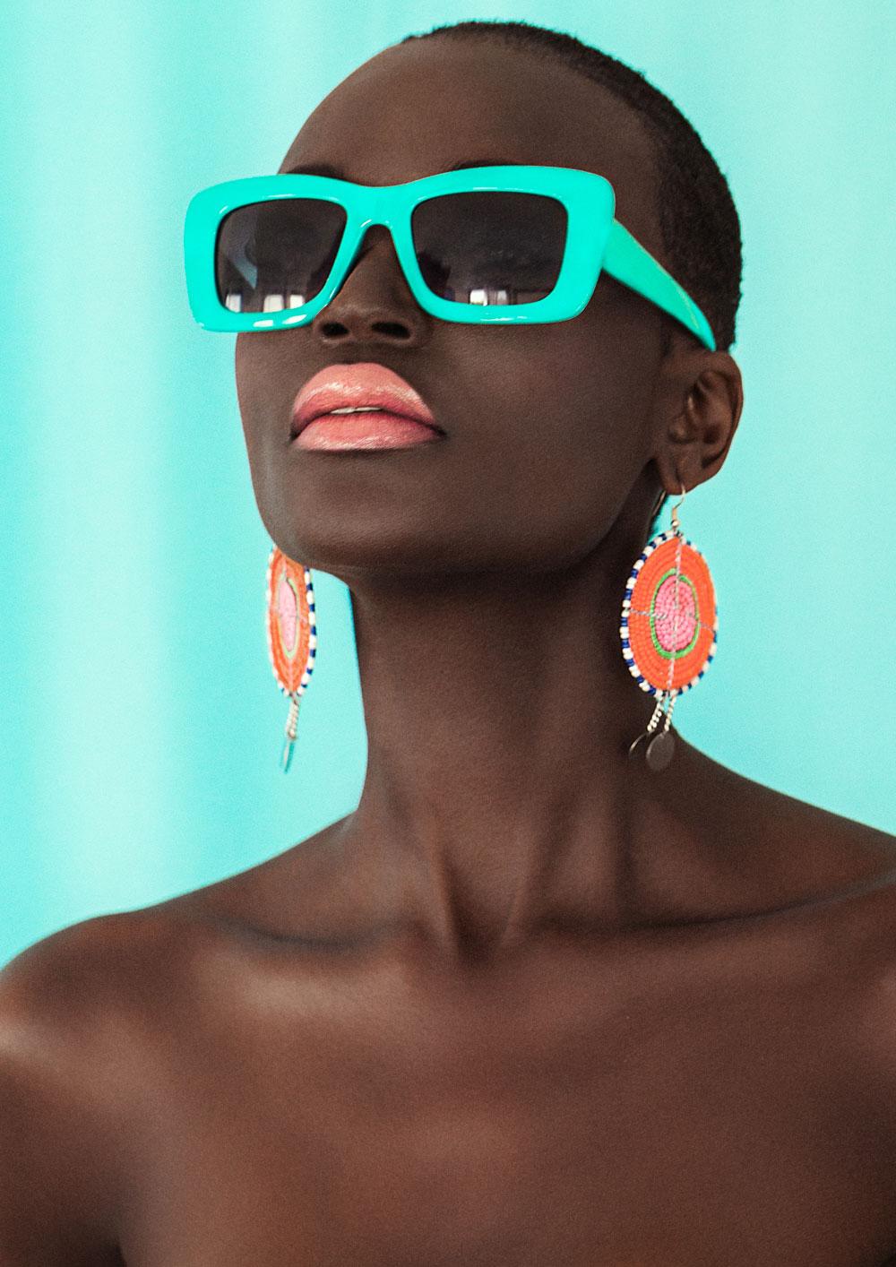 Πορτρέτο της γυναίκας με πορτοκαλί σκουλαρίκια και γυαλιά ηλίου.