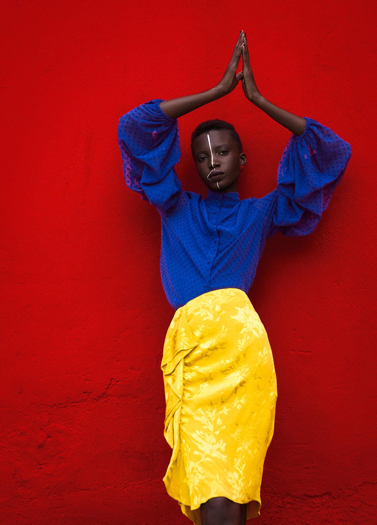 Ritratto di donna con gonna gialla e camicia blu davanti al muro rosso.