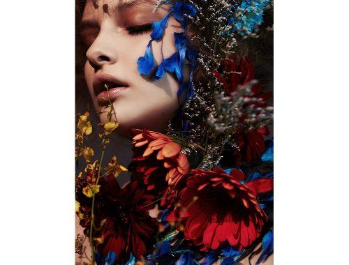 Portrett av kvinne med røde og blå blomster.