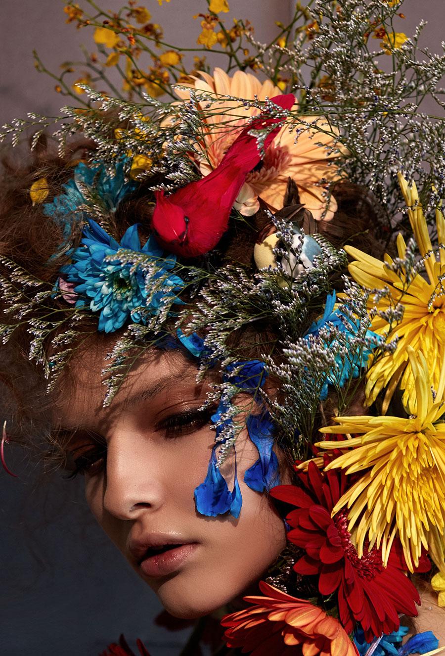 Ritratto di donna con copricapo floreale multicolore.