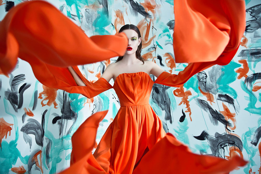 Vrouw met oranje jurk en rode lippen.