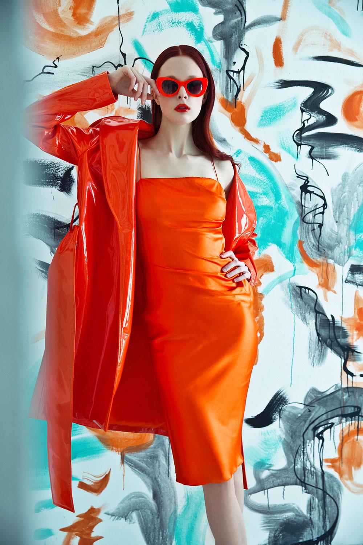 Kvinne som står med kjole og oransje regnfrakk.