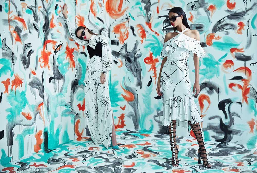 To kvinner står med mørke briller og hvit kjole.