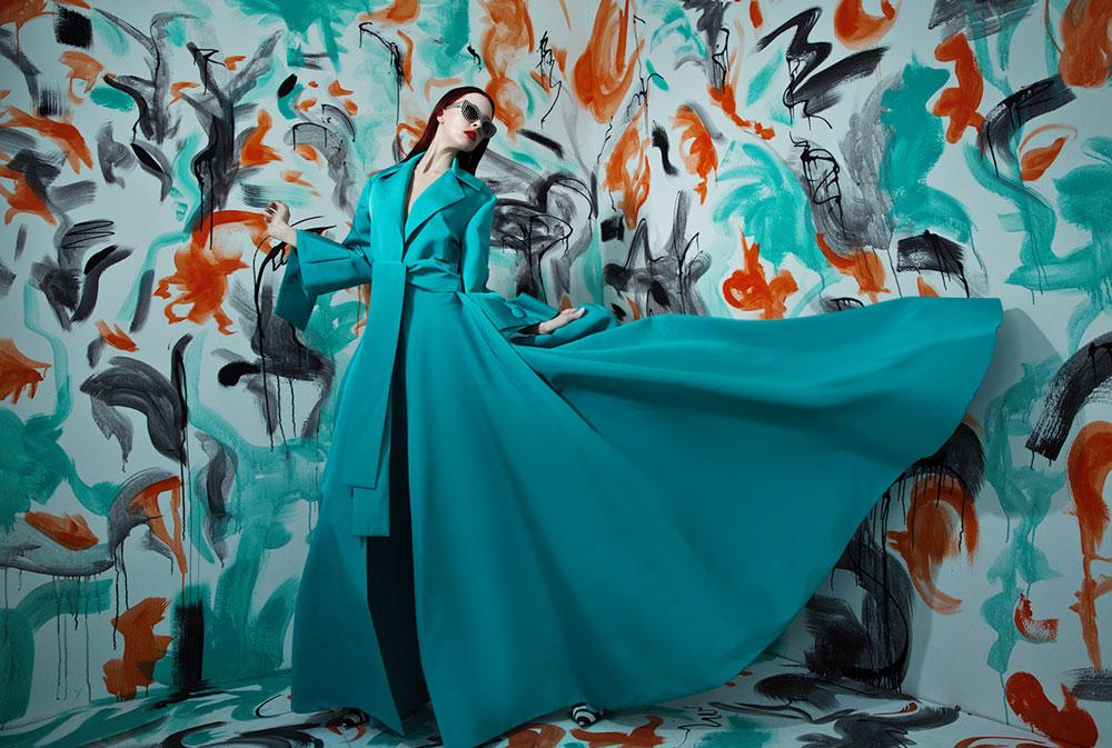 Vrouw in donkere glazen en blauwe jurk.