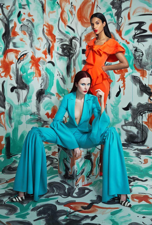 Kvinne sitter i blå kjole og dvs kvinne med rød kjole.