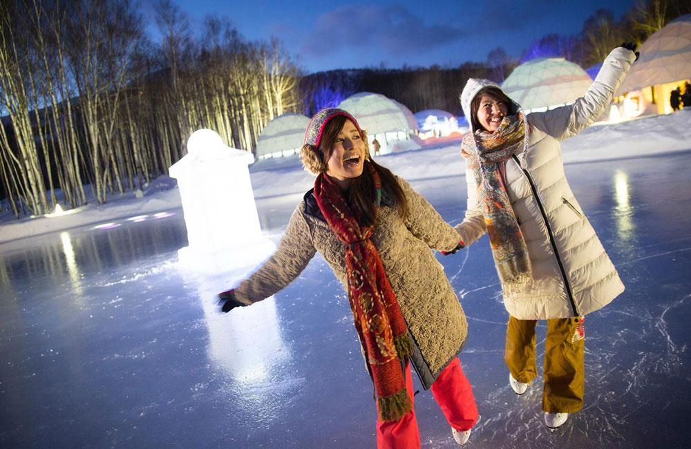 Mujeres con abrigos tomadas de la mano sobre pista de hielo.