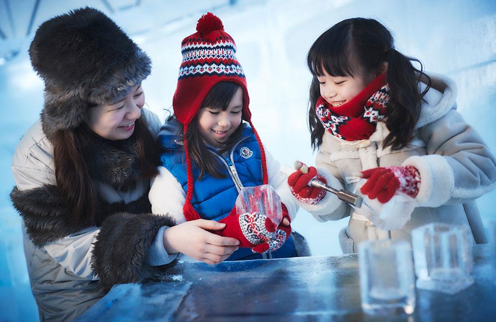Dos niñas y una mujer juegan con objetos de hielo.