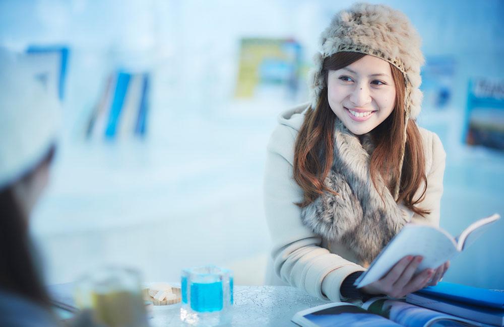 Mujer sonriendo con un libro en la mano.
