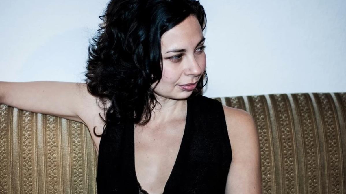 Mujer con blusa negra y cabello suelto sentada en un sillón.