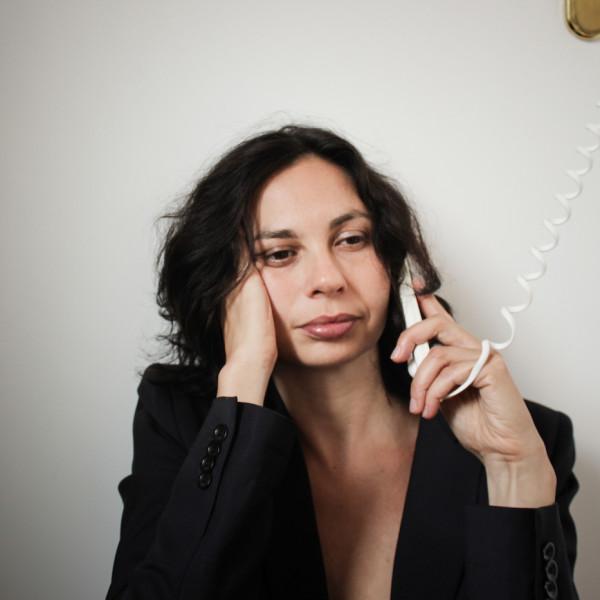 Mujer con la mano derecha en el rostro sostiene el auricular de un teléfono alámbrico color blanco.