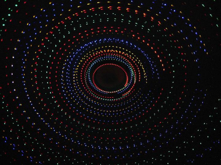 Series de luces navideñas forman círculos de colores sobre fondo negro.