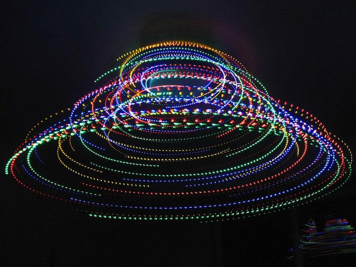 Formas circulares de luces de colores y fondo negro.
