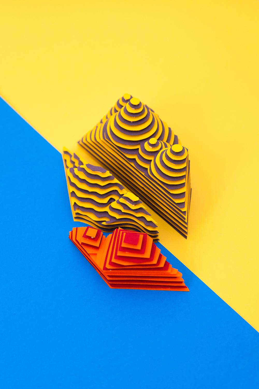 Fragmentos de esculturas amarillas y naranjas sobre fondo azul.
