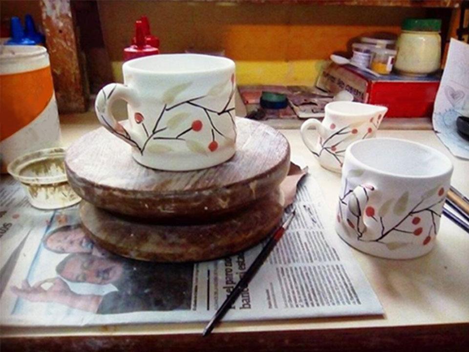 Drie keramische kopjes met de hand versierd op een tafel en een krant.