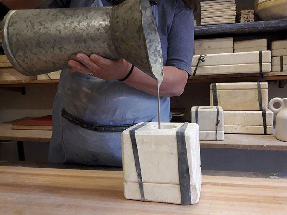 Man tømmer en væske inne i et keramisk stykke.