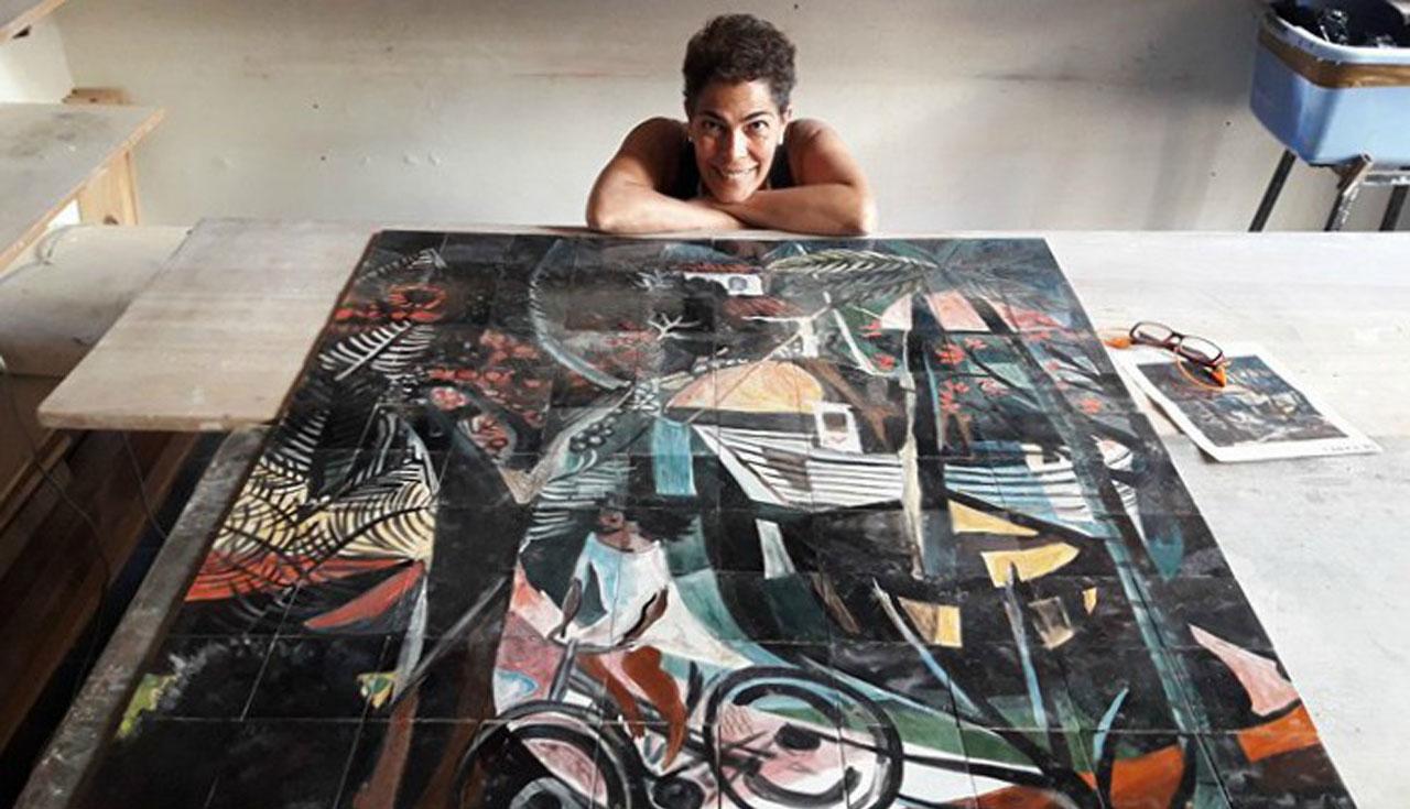 Kvinne hviler på bordet foran kunstverket.
