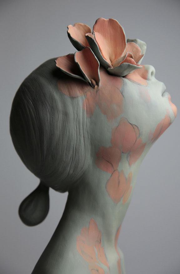 Grå skulptur av kvinne med rosa blomster.