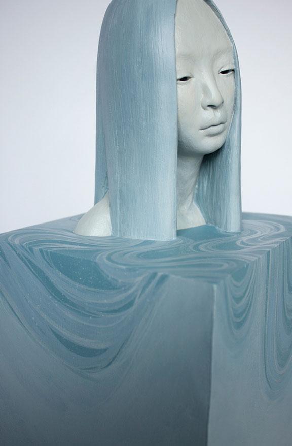 घन पर नीले बालों के साथ ग्रे महिला चेहरे की मूर्तिकला।