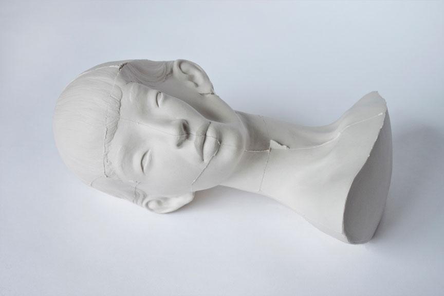 Skulptur av kvinnelig ansikt på hvit overflate.