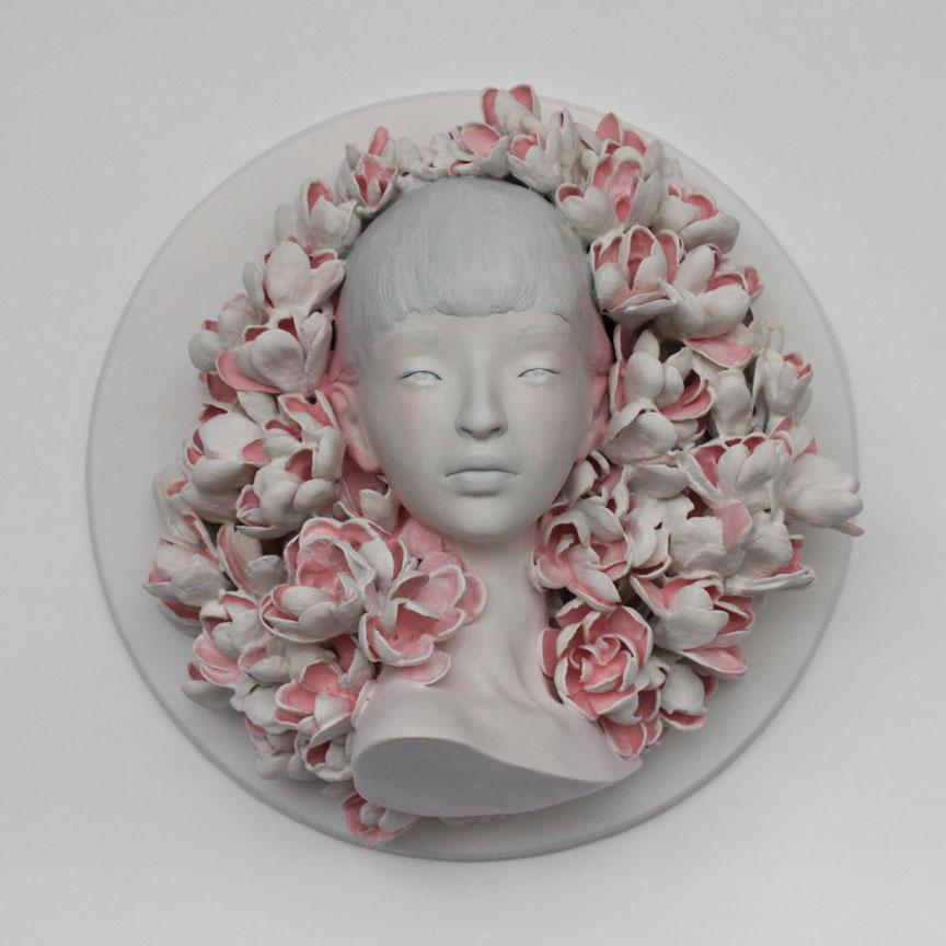 Skulptur av kvinnelig ansikt blant blomster.