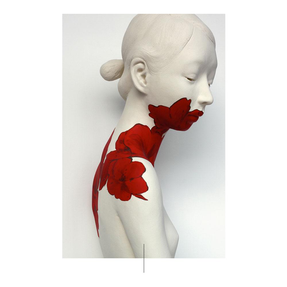 Escultura blanca de tordo femenino con flores rojas.