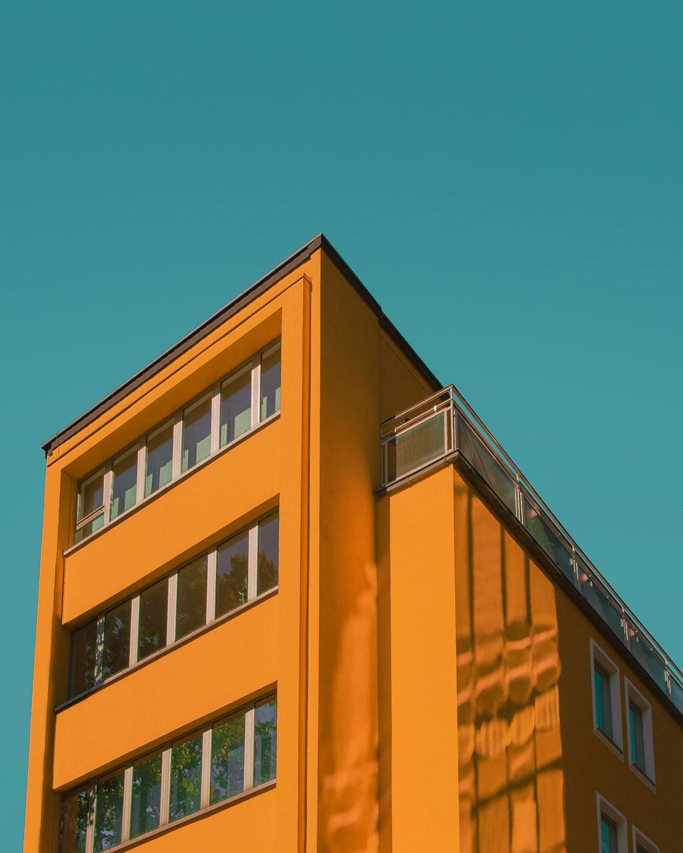 Exterior de edificio color naranja y cielo azul.