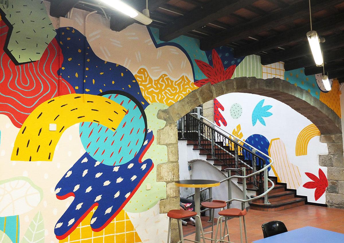 Interiør av en restaurant med vegger dekorert med arbeidet til Perrine Honoré.