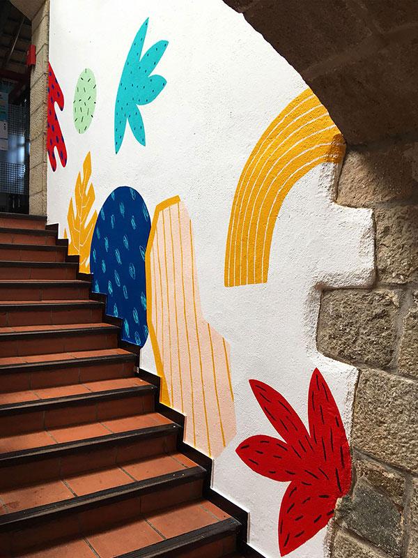 Hvit vegg med røde, gule og blå malerier.
